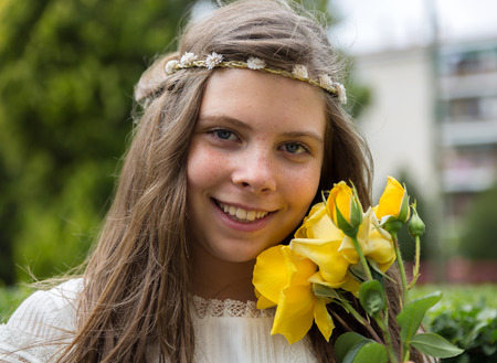 Beautiful blond girl smiles beside a pretty yellow flower, the day of her holy communion