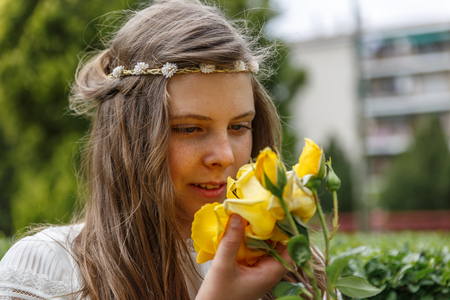 A beautiful girl carefully picks a pretty yellow flower in her hand, on the day of her holy communion