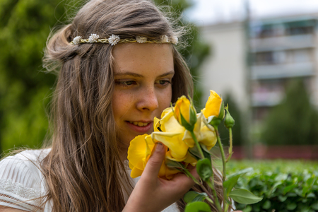 religious clothing: A beautiful girl with a large yellow flower in her hand, the day of her holy communion