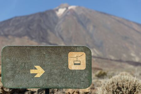 Green placard with the drawing of a cable car, with the Teide volcano in the background, Tenerife, Spain Stock Photo