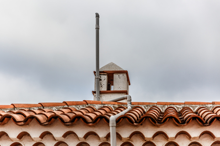 White chimney on a typical orange tile roof, on a cloudy day