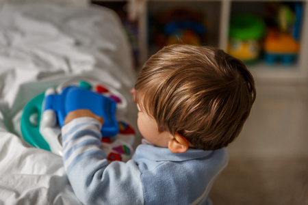 A cute little blond boy plays with a musical toy while in his room Stock Photo