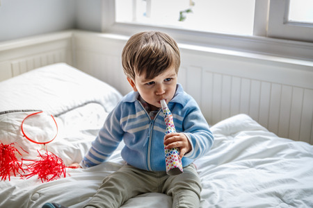 A little boy blows a whistle while on the bed in his bedroom