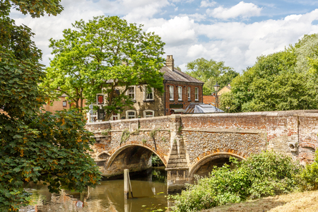 Beautiful view of a small bridge of stone and bricks with a lot of vegetation around, England
