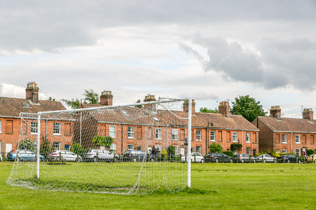 Football goal in a field in the city of Norwich with houses in the background, England