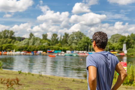 A man in a blue shirt contemplates a beautiful landscape from the edge of a river, UK