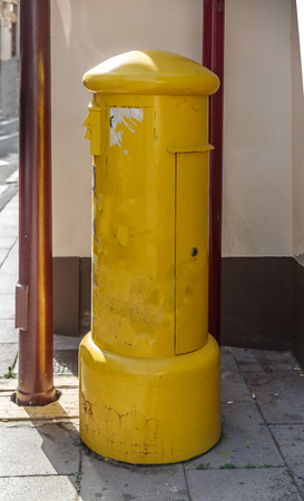 Yellow postbox on a street of a small town
