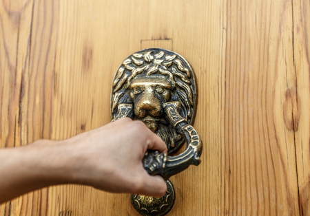 Hand knocking with an antique door knocker, on a wooden door