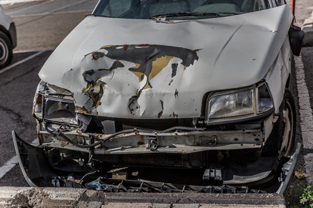 Front view of a wrecked white car, after a great accident