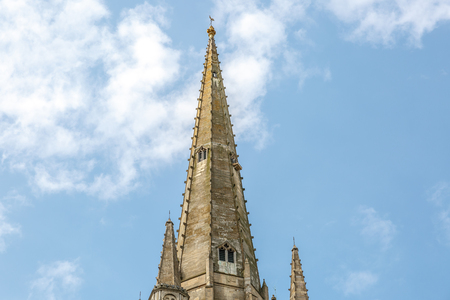 Tower of the medieval style catholic cathedral of the city of Norwich, with the blue sky in the background