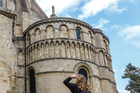 A tourist carefully observes the facade of part of the medieval style catholic cathedral in the city of Norwich, Norfolk, England Stock Photo