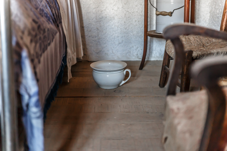 Old white urinal placed next to a bed in a bedroom in an old house Foto de archivo