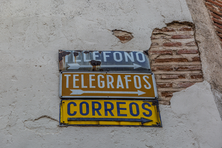 Telephone signs, telegraphs and post office in Spanish language, in a corner of a town in Spain