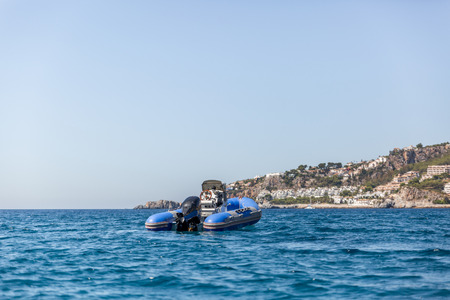Small motorboat of blue color moored in the sea near a beach, Spain