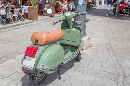 Scooter style motorcycle parked near an area with many restaurants, Europe
