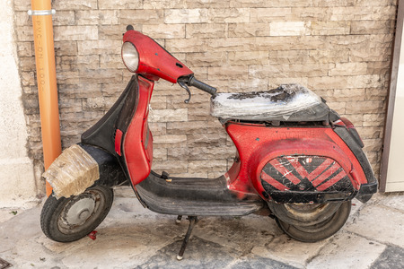 Very old red Italian style motorbike with many patches, parked in an old street Archivio Fotografico