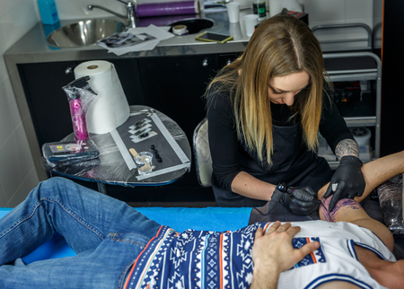A beautiful blonde girl tattooes the arm of a boy in her small tattoo studio