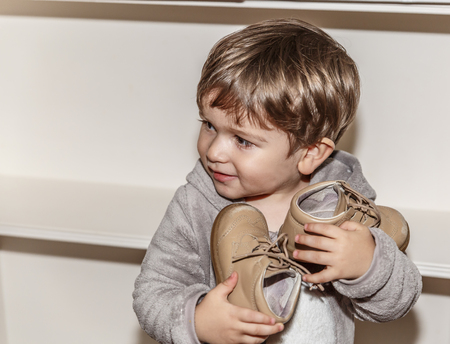 A cute little boy with a rogue face has his little brown shoes in his hands