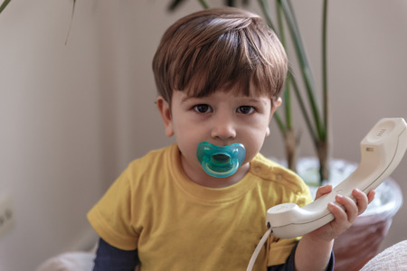 A cute child with a pacifier picks up the landline of his house to connect a call