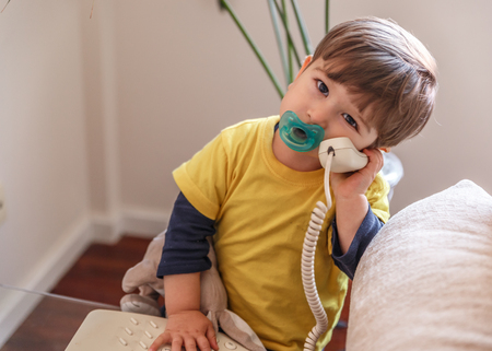 A cute child with a pacifier picks up the landline of his house to connect a call 스톡 콘텐츠 - 122031254