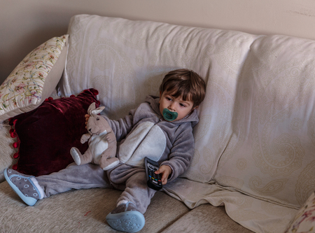 Little boy in his pajamas sitting on the living room couch with the control of the TV in one hand and a bunny in the other