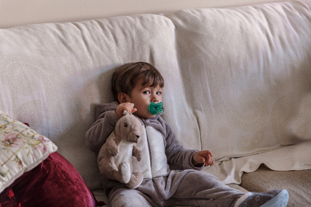 Cute boy in gray pajamas sitting on the big living room sofa with a bunny and a pacifier