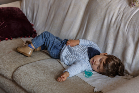 Cute boy dressed in blue, rests peacefully on sofa in the living room of his house