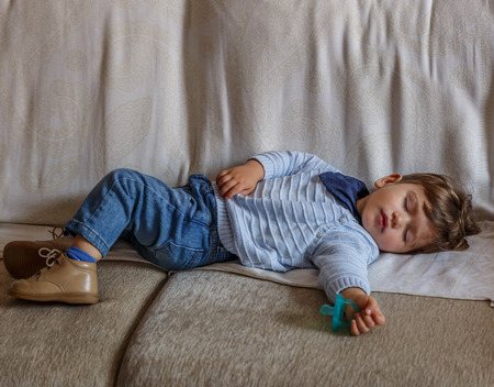 A tender little boy child dressed in blue, is resting peacefully on the big sofa in the living room of his home Stock Photo