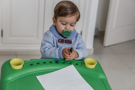 A little blond boy with a pacifier and dressed in blue, paints with crayons on a folio, while he is in his cozy bedroom
