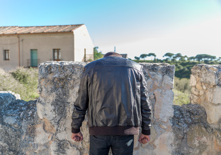A curious image of a man without a head wearing black pants and a leather jacket, leaning against an old battlement