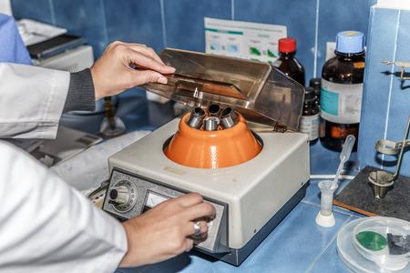A scientist regulates an agitator machine for test tubes in a laboratory Banco de Imagens - 121646929