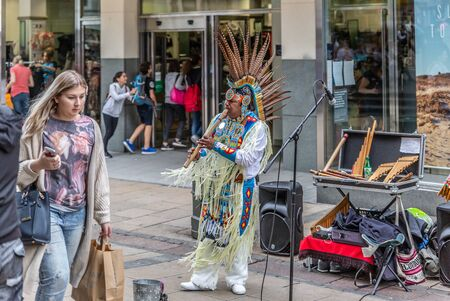 NORWICH, ENGLAND - JULY 8: A native Amazonian man plays music with a flute in a typical English pedestrian streeton July 8, 2016 in Norwich, England Éditoriale
