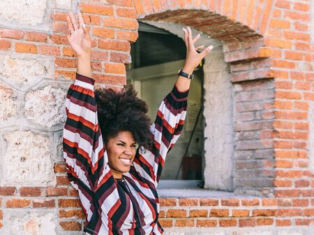 A pretty afro woman raises her arms and smiles, while leaning on a brick wall next to a window of a large building