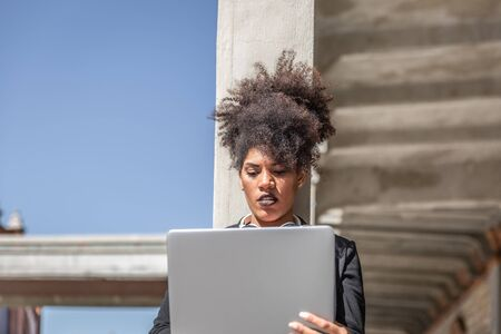 Attractive girl with black jacket, headphones around neck and afro hair, is concentrated with her laptop while leaning on an outdoor column on a sunny day