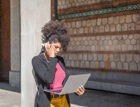 Beautiful afro haired brunette woman with black jacket, listens to something in her headphones while checking something on her laptop next to a building