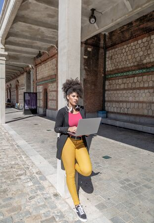 Attractive brunette girl with afro hair and headphones around her neck, is thoughtful while working with her laptop resting on a column of a city building Stock fotó