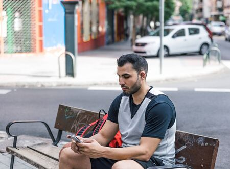 Athlete boy writes something on his mobile phone, while sitting on a bench in a big city Foto de archivo - 135425744
