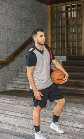 Strong and attractive basketball player leaves the portal of a large building with a basketball and a backpack Foto de archivo - 135425785