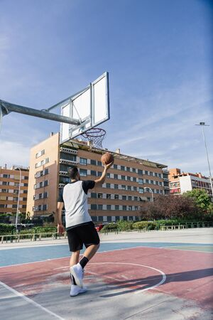 On an outdoor urban court, strong athlete plays basketball alone with an orange ball