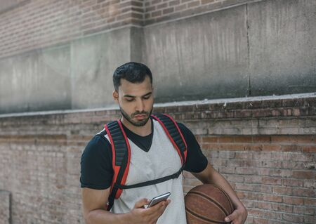 Strong man of athletic body with a red backpack and a basketball, walks relaxed checking his mobile phone