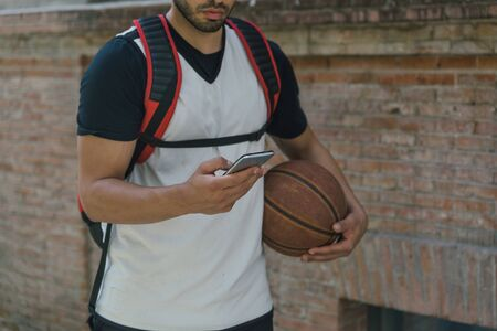 Body view of an athlete carrying a basketball and checking something on his smartphone, while walking down the street