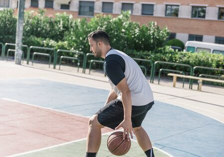 Sportsman is playing basketball very concentrated on an outdoor court, to keep track of his ball