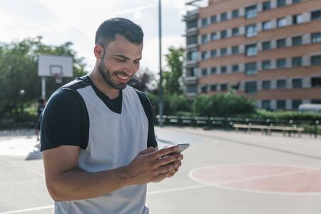 Attractive sportsman man looks at his mobile phone while taking a break in the middle of an urban court on a sunny day