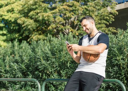 Attractive latin man basketball player with a ball looks at his mobile phone and smiles while taking a break next to a leafy tree