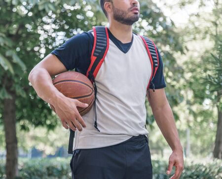 Forefront of an athlete basketball player with his orange ball and a backpack behind his back walking through a park Stock Photo