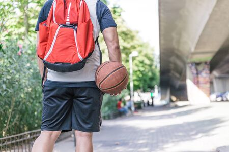Back view of a male basketball player carrying his ball and a large red backpack on his back that walks through a park on a sunny afternoon