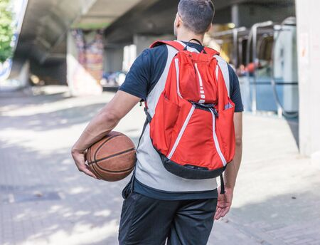 Back view of a strong build basketball player carrying a large red backpack and a basketball while walking through a city