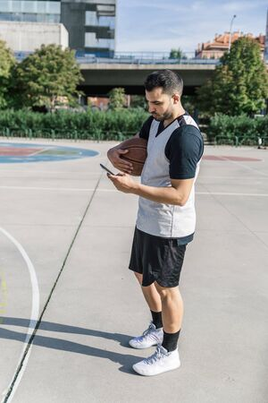 An attractive basketball player takes a break and looks at his mobile phone while on an outdoor court