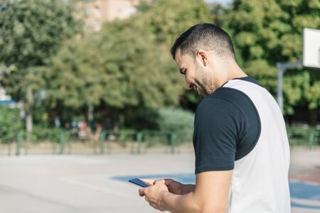 Strong athlete man checks his mobile phone in the middle of an outdoor basketball court