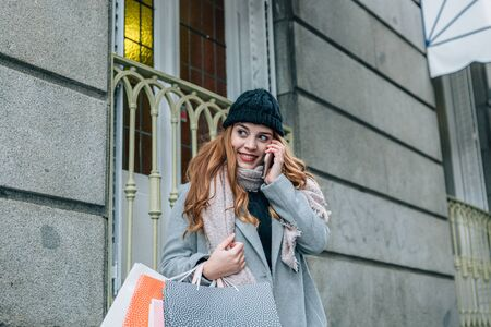 Beautiful European blonde girl with coat, speaks on her mobile phone, while shopping and carries a bag